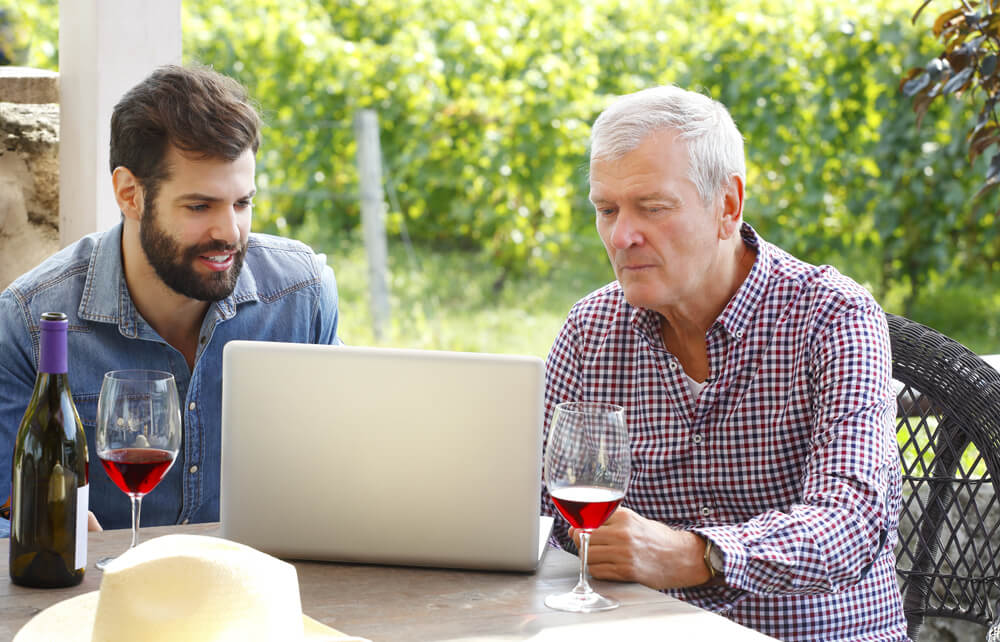 Two men drinking wine while looking at laptop